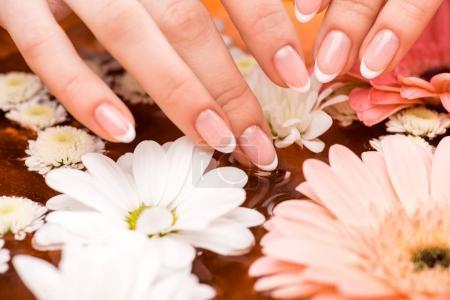 Photo pour Vue recadrée de femme faisant des procédure de spa avec des fleurs pour ongles - image libre de droit