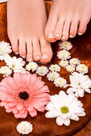 Photo pour Recadrée vue de femme faisant le bain avec des fleurs pour pieds - image libre de droit