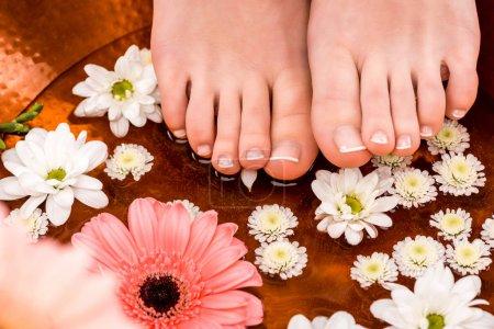 Photo pour Recadrée vue de femme faisant des procédure de spa avec des fleurs pour pieds - image libre de droit