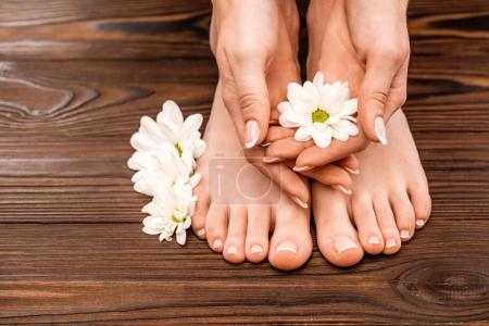 Photo for Cropped view of female hands and feet with medicine and pedicure on wooden surface - Royalty Free Image