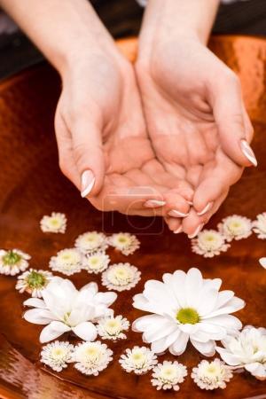 Photo pour Vue recadrée de femme faisant le bain avec des fleurs pour ongles - image libre de droit