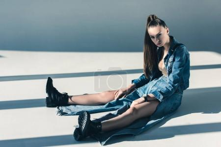 beautiful young woman in denim clothes sitting on floor