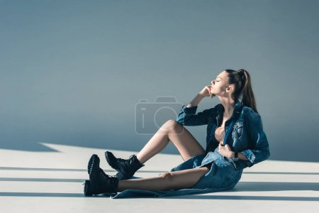 attractive woman in denim clothes sitting on floor