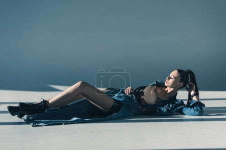 beautiful woman in denim clothes lying on floor with shadows