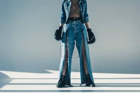 cropped view of woman in denim clothes with boxing gloves