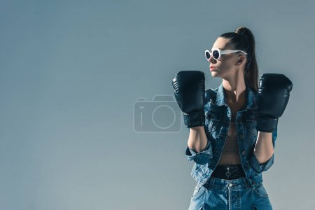 stylish girl in denim clothes and sunglasses posing with boxing gloves, isolated on grey