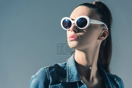 beautiful stylish woman in denim clothes and sunglasses, isolated on grey