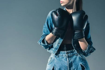 partial view of stylish girl posing with boxing gloves, isolated on grey