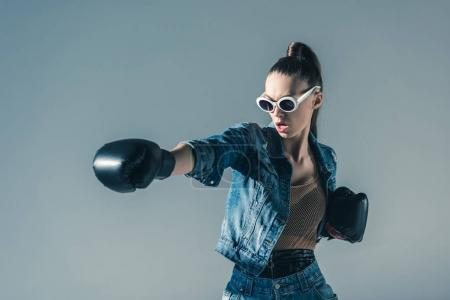 stylish boxing girl in denim clothes and sunglasses, isolated on grey