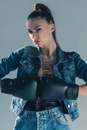stylish model in denim clothes and boxing gloves, isolated on grey