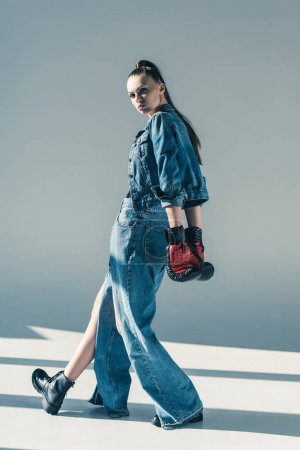 stylish girl in denim clothes and boxing gloves posing for fashion shoot