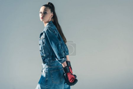 stylish brunette girl in denim clothes and boxing gloves, isolated on grey