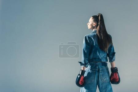 Photo for Rear view of model in denim and boxing gloves, isolated on grey - Royalty Free Image
