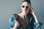 fashionable girl posing in denim clothes and sunglasses, isolated on grey