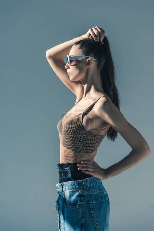 Photo for Beautiful girl posing in sunglasses with ponytail hairstyle, isolated on grey - Royalty Free Image