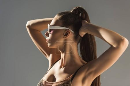 beautiful girl posing in sunglasses with ponytail hairstyle, isolated on grey