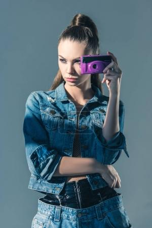 brunette girl posing in denim clothes with retro camera, isolated on grey