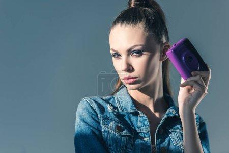 Photo pour Belle fille posant dans les vêtements de denim avec caméra rétro, isolé sur fond gris - image libre de droit