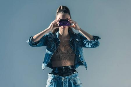 fashionable girl posing in denim clothes with retro camera, isolated on grey