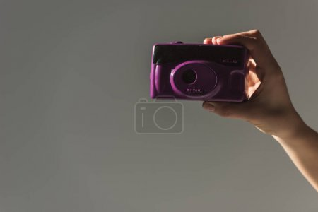 cropped view of female hand holding purple photo camera, isolated on grey