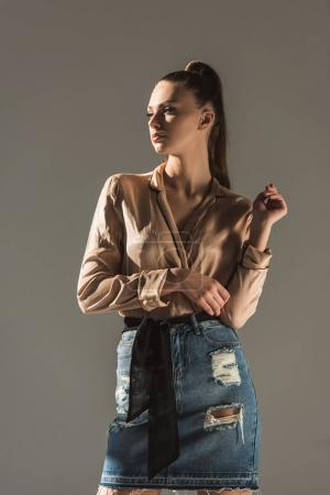 attractive girl posing in blouse and denim skirt, isolated on grey