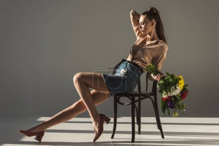 fashionable elegant girl with bouquet of flowers posing on chair