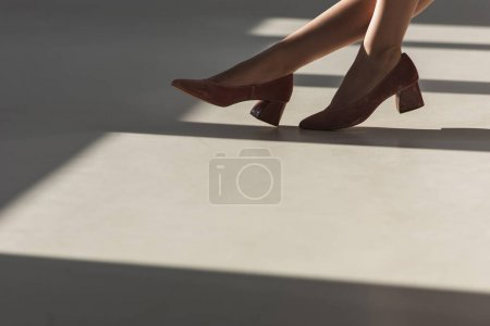 cropped view of fashionable girl posing in red shoes