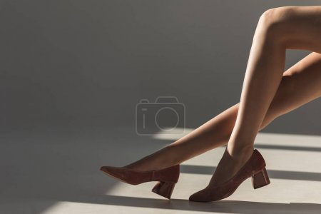 cropped view of girl posing in trendy red shoes