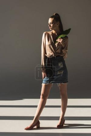 stylish woman in denim skirt and blouse holding green leaf