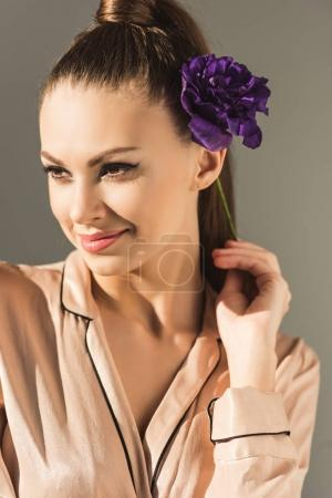 fashionable smiling woman with purple flower, isolated on grey