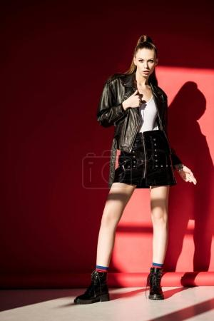 stylish beautiful girl posing in black leather jacket for fashion shoot on red