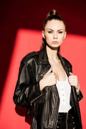 fashionable young woman posing in black leather jacket and looking at camera, on red