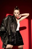stylish caucasian girl posing in black leather jacket for fashion shoot on red