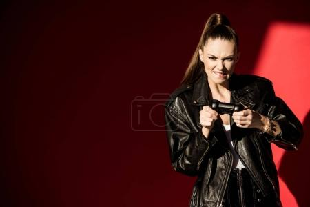 beautiful girl in black leather jacket playing video game with joystick, on red