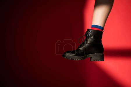 Photo for Cropped view of female leg in black shoe on red - Royalty Free Image