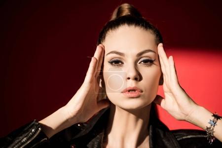 Photo pour Belle fille avec la coiffure queue de cheval posant pour Shooting de mode sur le rouge - image libre de droit