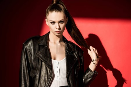 Photo for Stylish girl with ponytail hairstyle posing in black leather jacket for fashion shoot - Royalty Free Image
