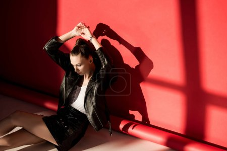 stylish girl posing in black leather jacket for fashion shoot on red