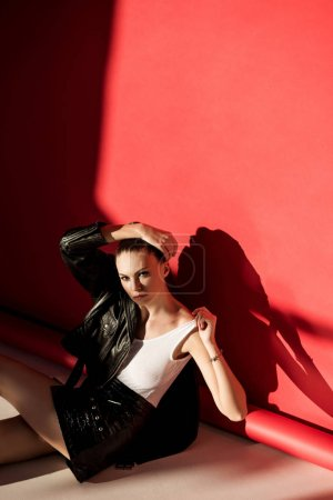 beautiful young woman posing in black leather jacket for fashion shoot on red