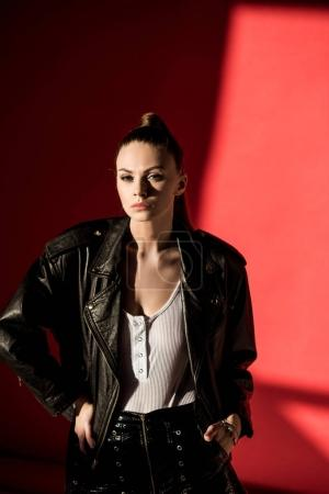 Photo for Attractive young woman posing in black leather jacket for fashion shoot on red - Royalty Free Image