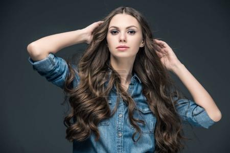 attractive girl with long hair posing in denim shirt, isolated on grey