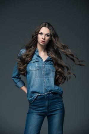 Photo pour Jolie fille avec les cheveux longs posant en jeans, isolé sur gris - image libre de droit