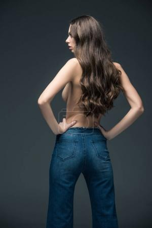 back view of half naked woman with long hair posing in jeans, isolated on grey