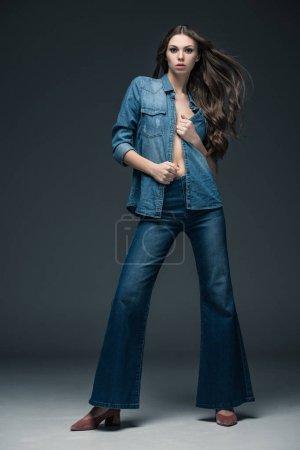 Photo pour Jolie fille sexy posant dans des vêtements de denim, sur fond gris - image libre de droit