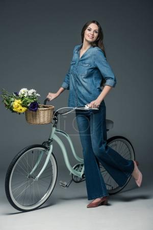 beautiful girl in denim clothes holding bike with flowers in wicker basket, on grey
