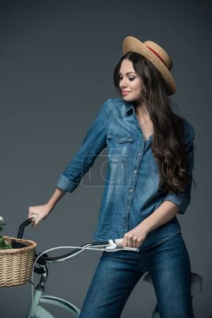 attractive girl in denim clothes and straw hat standing with bicycle, isolated on grey