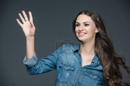 attractive cheerful girl waving isolated on grey