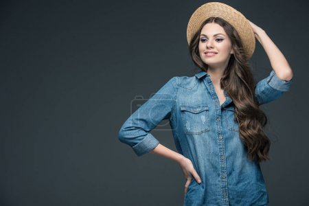 pretty cheerful girl in denim shirt and straw hat, isolated on grey