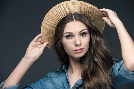 beautiful girl in denim shirt and straw hat, isolated on grey