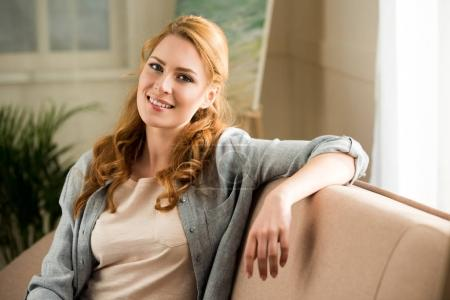 Photo pour Belle jeune femme assise sur le canapé et souriant à la caméra - image libre de droit